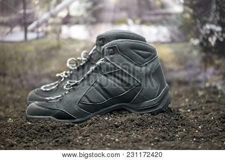A Pair Of Black Walking Boots On The Ground