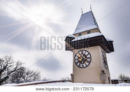 Sun Flares Over Snow Covered Uhrturm Clocktower Landmark Of City Graz On Hill Schlossberg In Winter