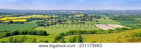 English summer rural panorama with fields and cottages as viewed from South Downs hill in  Sussex, Southern England, UK