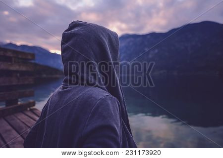 Lonely Hooded Female Person Standing By The Lake And Looking At Beautiful Mountain And Forest Landsc