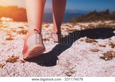Female Athlete Hiking On Mountain Rocky Path. Young Woman With Athletic Sneakers Jogging Or Running