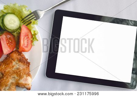 Tablet Computer With Blank Isolated Screen And Dish With Fresh Salad On The Restaurant Table Backgro
