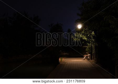 Double Exposure Night Scene Of Person Sitting In The Dark Street Under Streetlights. The Receding Ma