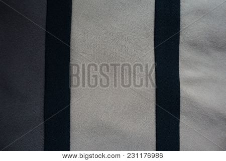 Two Vertical Black Ribbons Sewn To Grey And Beige Fabric