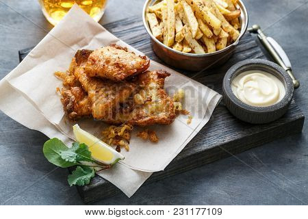 British Traditional Fish And Chips With Tartar Sauce On Crumpled Paper