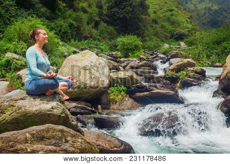 Woman doing yoga meditation asana Padmasana lotus pose outdoors at tropical waterfall