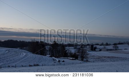 Winter Agricultural Background Of A Dairy Farm Nestled In Snow-covered Hills.