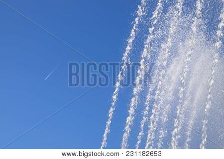Jets And Splashes Of Water Fountain Against The Blue Sky. Condensation Track Of A Jet Plane Against