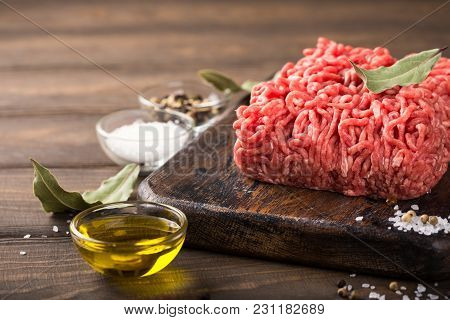 Fresh Raw Beef Minced Meat With Salt, Pepper, Olive Oil And Laurel Leaves On Dark Wooden Board. Heal