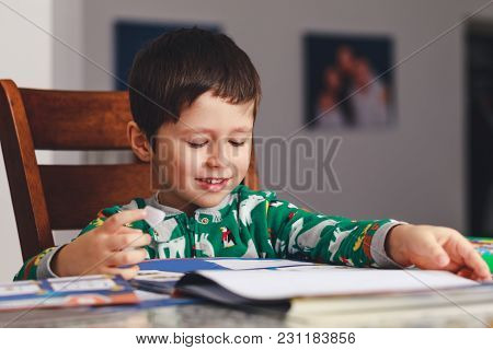 Young Little Boy Reading A Book While Sitting At Table, Indoor Shoot. Little Boy Having Fun During S