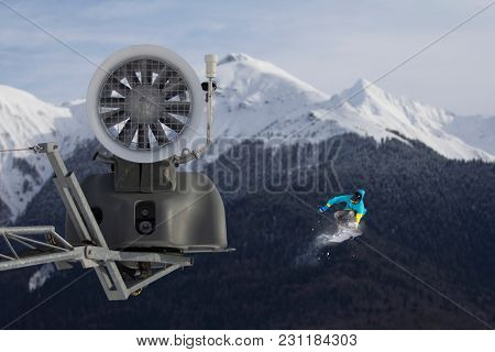 Snow cannon in the mountain ski resort and the flying snowboarder.