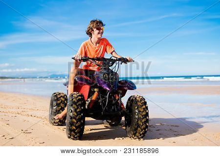 Teenager Riding Quad Bike On Beach