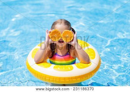 Child In Swimming Pool. Kid Eating Orange.