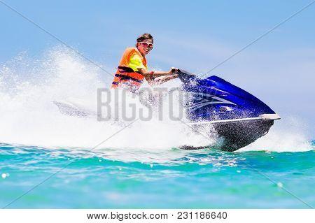 Teenager On Jet Ski. Teen Age Boy Water Skiing.