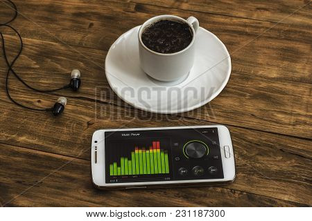 On The Wooden Surface There Is A Cup Of Black Coffee On A Saucer, Next Are Headphones And A Smartpho