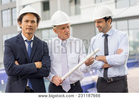 Closeup Portrait Of Three Content Diverse Business People Wearing Helmets, Discussing Issues, Holdin