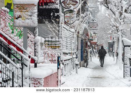Montreal, Ca - 14 March 2018: Pedestrian On Saint Denis Street During Snowstorm