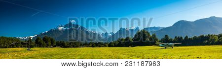 Airport with green grassy runaway in the rural area among the Patagonian mountains, Chile
