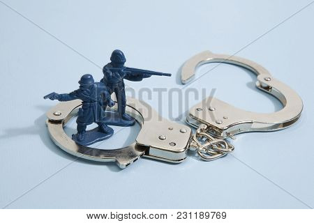 Isolated Handcuffs Besieged Plastic Toy Soldiers On A Pop Vibrant Blue Color Background. Minimal Col