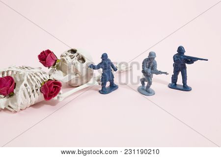 Plastic Toy Soldiers Around A Pop Skeleton Wearing Flower Roses On A Pop Vibrant Pink Background. Mi