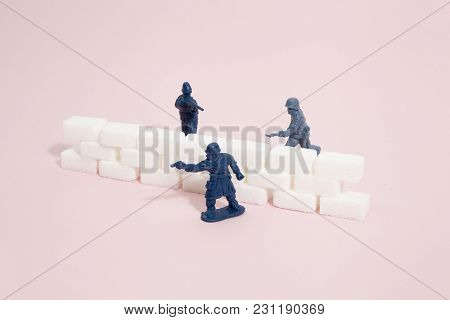 Battlefield With Plastic Soldiers Separated By A Wall Border Of White Sugar Cubes. Minimal Color Sti