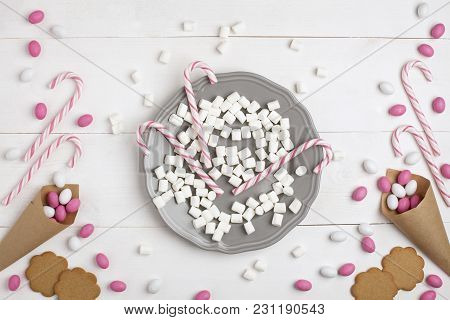Frame Colorful Candies, Striped Lollipops And Cookies In The Form Of Heart On Plate Top View White W