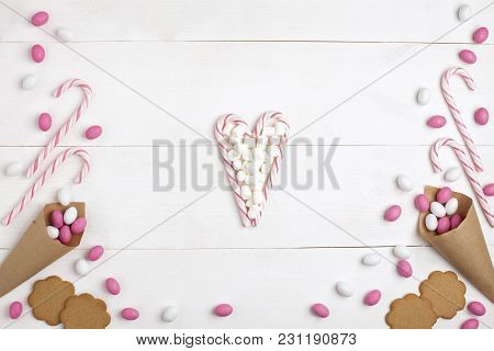 Frame Colorful Candies, Marshmallows, Cookies And Striped Lollipops In The Form Of Heart Top View Wh
