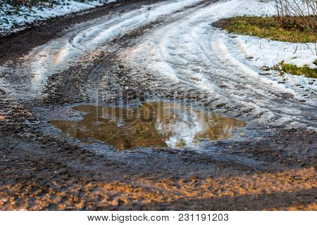 Small Puddle On The Road, Reflection In Water Near The Meadow. Snow And Winter