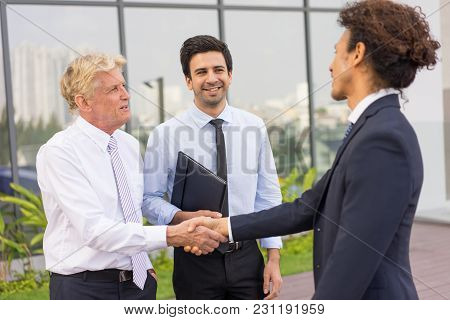 Closeup Of Three Smiling Diverse Business People Shaking Hands And Standing Outdoors With Building I