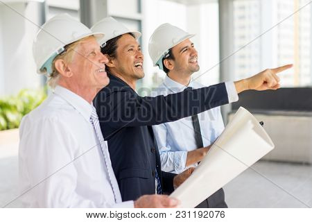 Closeup Portrait Of Three Smiling Diverse Business People Wearing Helmets, Holding Blueprint, Discus