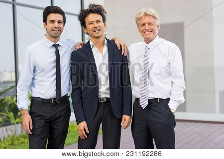 Closeup Of Business Team Of Three Smiling Diverse People Looking At Camera, Embracing And Standing O