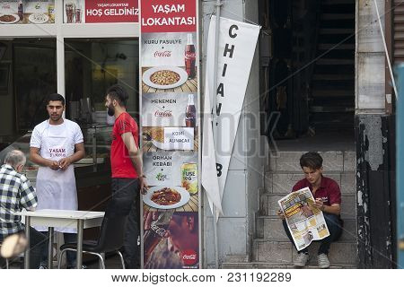 Istanbul Turkey 05 July 2017 The Waiter Serves Visitors In A Street Cafe. A Young Man Reading A News