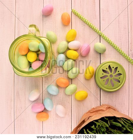 Green Transparent Glass Jar With Colored Easter Eggs On The White Wooden Table Background, Decorativ