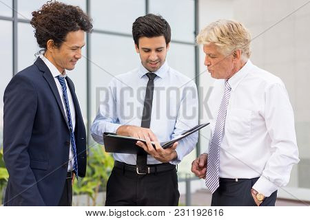 Closeup Of Three Smiling Diverse Business People Discussing Issues, Looking Through Document In Fold