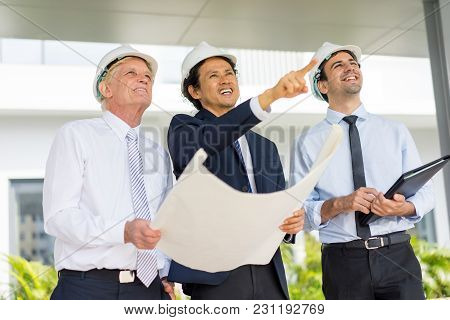 Closeup Portrait Of Three Happy Diverse Business People Wearing Helmets, Holding Blueprint, Discussi