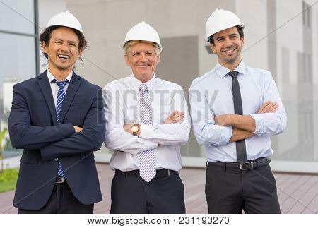 Closeup Of Three Smiling Diverse Business People Looking At Camera, Wearing Helmets And Standing Wit