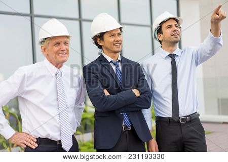 Closeup Portrait Of Three Smiling Diverse Business People Wearing Helmets, Looking At Something And