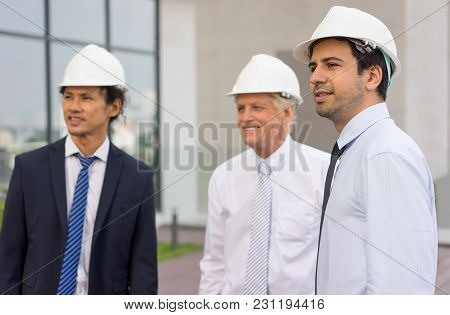 Closeup Of Three Smiling Diverse Business People Looking Away, Wearing Helmets And Standing Outdoors