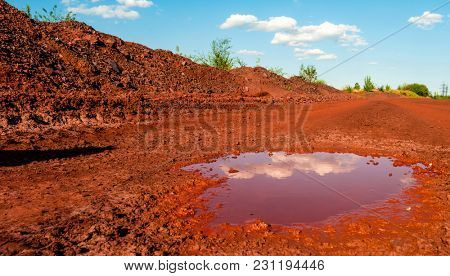 Reflection of the clouds in small puddle on dry red soil in Kryvyi Rih, Ukraine