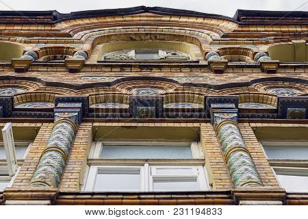 Bottom View Of Old, Historical Building. Front Window Of Structure, Edifice With Classical Mosaic Ar