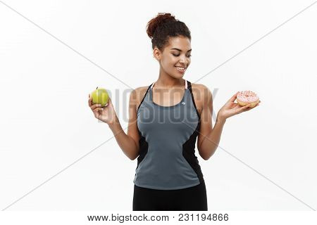 Healthy And Diet Concept - Beautiful Sporty African American Make A Decision Between Donut And Green