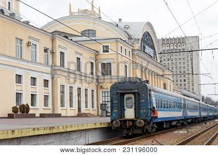 Kharkiv, Ukraine - March 25, 2012: Passenger train near the platform of the Kharkiv Passenger Railway Station. Passenger train lines. Ukrzaliznytsia passenger coaches cars.