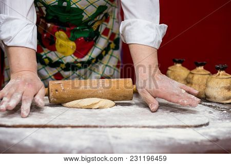Close Up Of Female Baker Hands Kneading Dough And Making Bread With A Rolling Pin. Cooking Process C