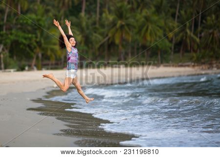 Young woman runs jumps into the sea on a tropical beach.