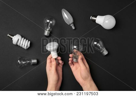 Woman holding LED and incandescent lamp near different light bulbs on dark background