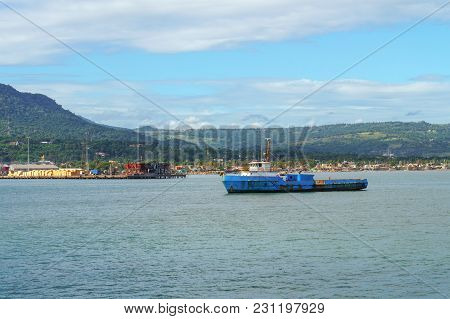 Blue Floating On The River Barge Against The Cargo Port