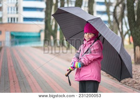 Little Cute Caucasian Girl In Hat And Jacket Walking Under Umbrella In A City Park During Rain.