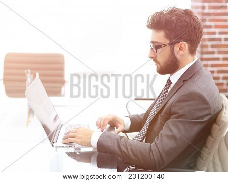 businessman working in bright office, sitting at desk