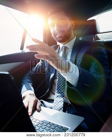 businessman sitting in the back seat in the car and pointing his finger forward