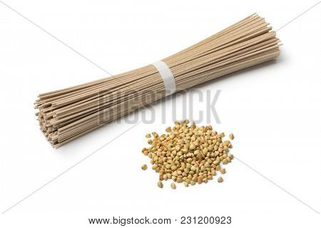 Heap of dried buckwheat seeds and buckwheat noodles isolated on white background